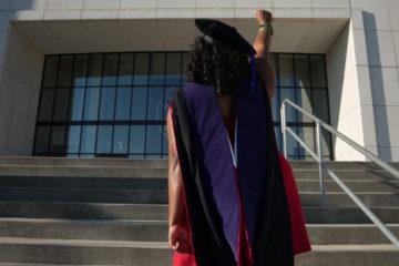graduate in PhD regalia raising fist in front of building